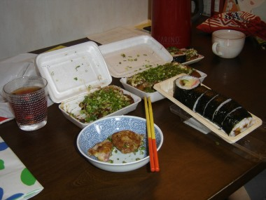 "Some ""tako yaki"", fried octopus dumplings, covered in scallions. And futomaki sushi nori rolls."