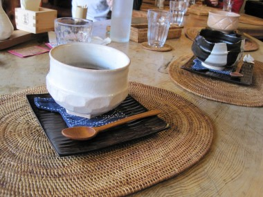 Desert at Yaokan, Kyoto, Japan in lovely bowls, with wooden spoons, wooden plate, and a blue cloth coaster in the shape of a shirt.