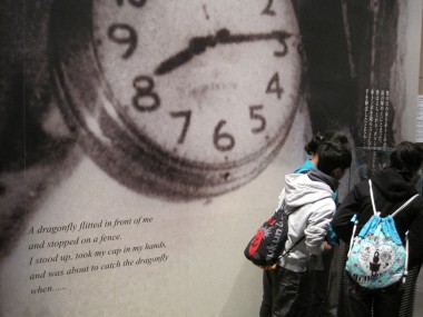 Hiroshima Peace Memorial Museum - Japanese school kids looking at a watch that froze at the exact time the first atomic bomb was dropped at 8:15 a.m., August 6th, 1945. A quote from the owner of the watch is seen in English on the left and Japanese on the right.