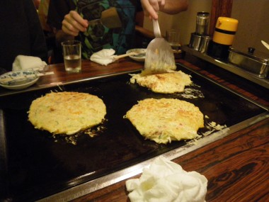"Okonomiyaki: Eli, Sarah and David had okonomiyaki, Japanese pancakes ""fried as you like it"" in Kyoto, Japan. David's flipping his over."