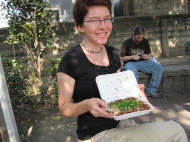 Rachel showing off the delicious tako yaki covered in mayonnaise and scallions.