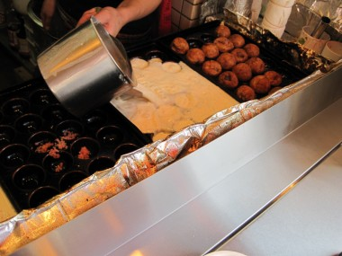Tako yaki, fried octopus dumplings, being made in my old neighborhood of Mikuni, Osaka, Japan. The finished one are on the right.