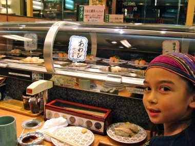 Yuni in front of the sushi conveyor belt.
