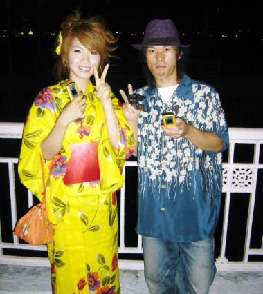 A woman in a yukata, light summertime version of the kimono, and a man with that style of shirt at a fireworks festival in Osaka.