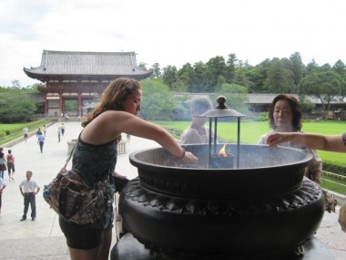 """Nadia offering incense in front of the Great Buddha statue, the """"Daibutsuden"""", in the Todaiji Temple in Nara, Japan. This is a common practice at Buddhist temples in Japan."""