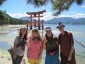 Standing in front of the famous huge Shinto torii gate of the Itsukushima Shrine on Miyajima Island in Hiroshima Bay, Japan. It's one of the most famous views in Japan.