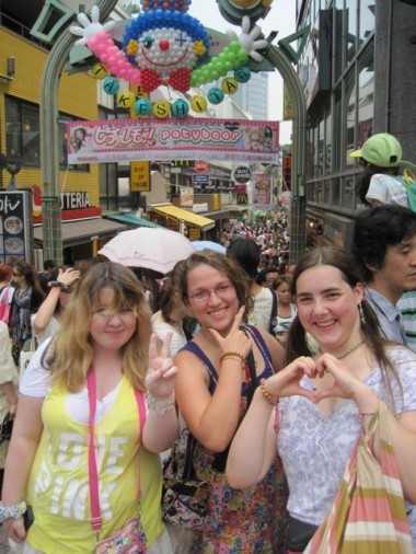 The girls posing for the photo in various Japanese ways in front of Takeshita Dori (street), in Harajuku, Tokyo, one of the fashion capitals of the world.